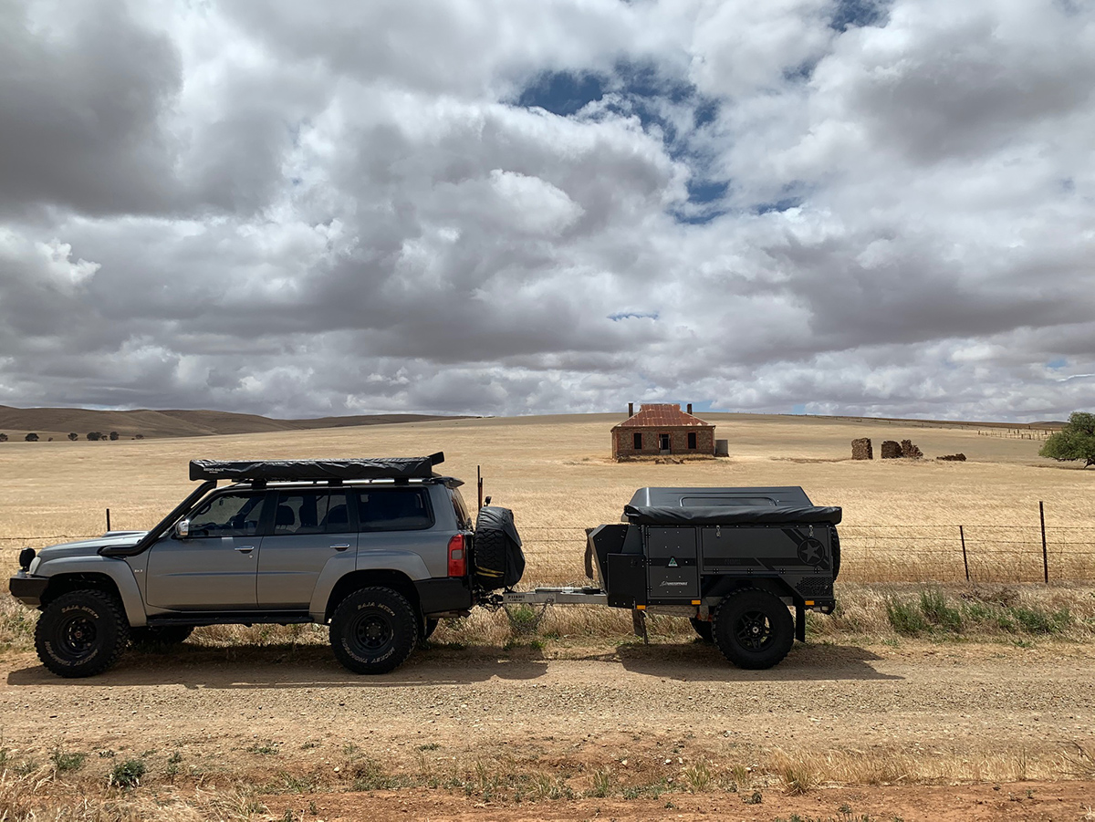 4WD towing a Patriot Camper parked on the side of a country road with a derelict farmhouse in the distance.