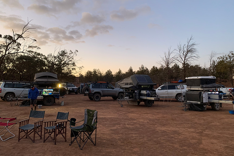 A campsite at dusk, with a number of 4WDs parked among Patriot Campers