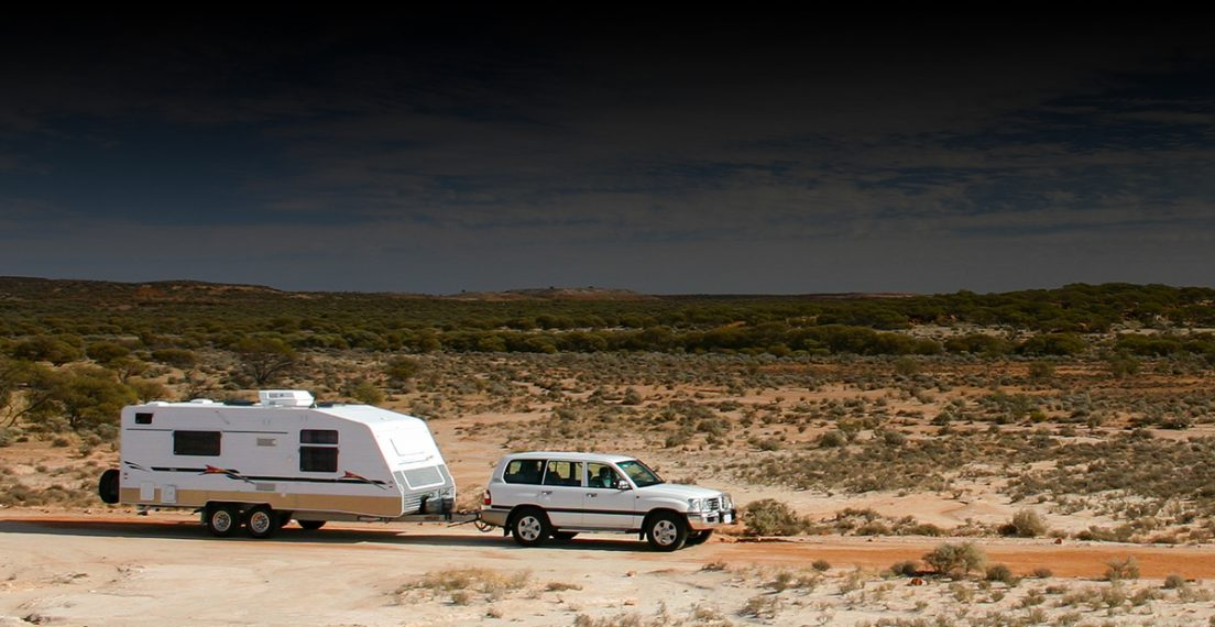 An SUV towing a large caravan is pictured in the arid outback of australia